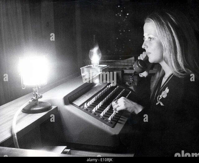 Telephone operator working by emergency lighting in a telephone center during the 1973 oil crisis in London, England - Stock Image