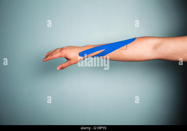 A man's arm with kinesio tape on it - Stock-Bilder