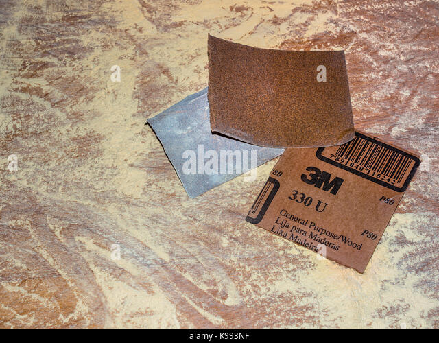 Sandpaper and sawdust on table top. - Stock Image