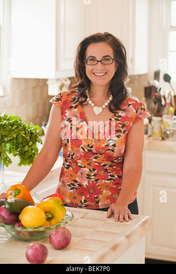 Portrait of a mid adult woman smiling at a kitchen counter - Stock-Bilder