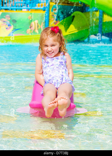 Smiling cheerful baby girl enjoying water attractions, warm sunny day, swimming in poolside, carefree childhood, - Stock-Bilder