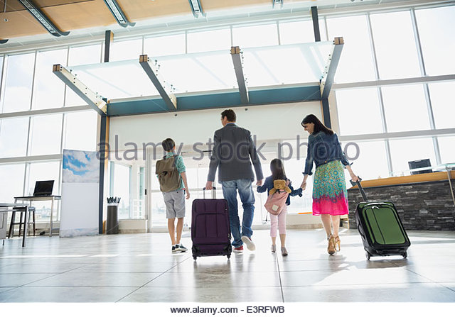 Family with suitcases leaving airport - Stock-Bilder