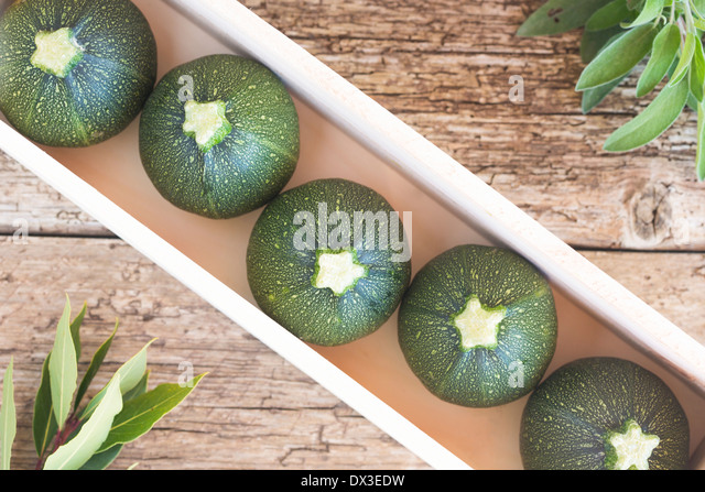 raw courgettes in wood box, with bay leaves and sage herbs on a rustic wood board - Stock Image