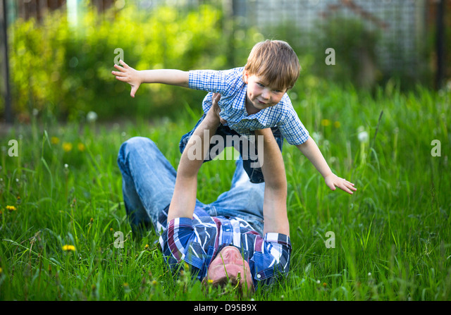 Father and son playing lying on the grass in the park - Stock Image