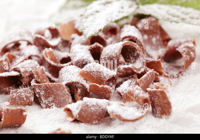 Chocolate curls sprinkled with powdered sugar - Stock Image