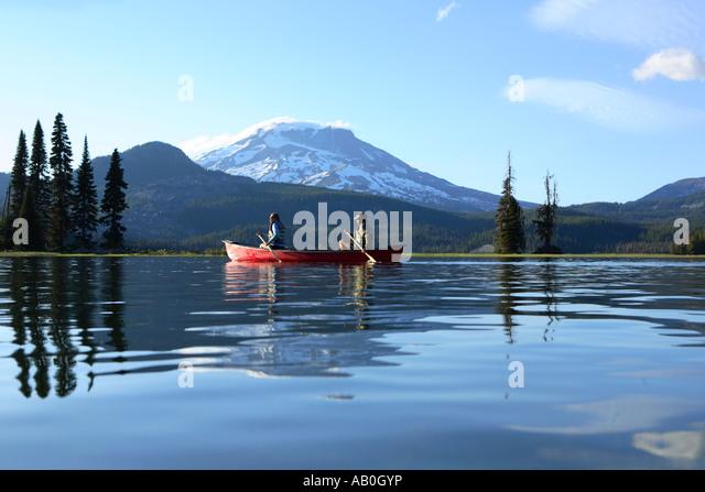 Couple paddling canoe on lake - Stock Image
