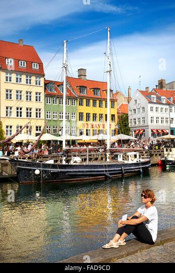 Turist relaxing at Nyhavn Canal, Copenhagen, Denmark - Stock-Bilder