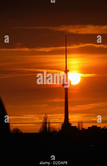 The Alexanderplatz television tower silhouetted against a beautiful sky with the sun setting - Stock Image