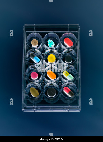 A variety of drugs sitting in a multi well sample tray Illustrating drug clinical trial - Stock Image