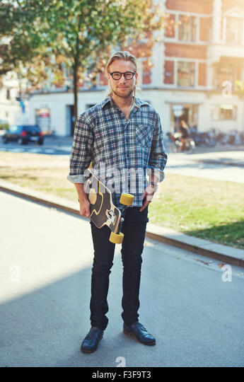 Hipster style portrait of young man. Stylish man with long blond hair - Stock Image