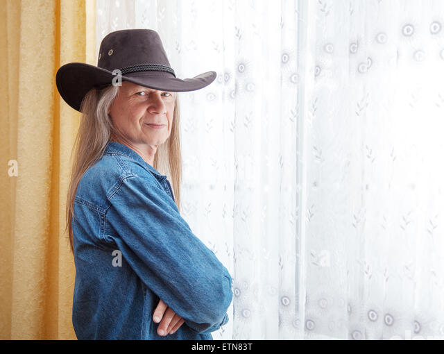 Portrait of a mature man with long hair and a cowboy hat - Stock Image