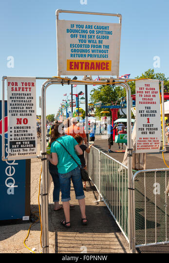 Rules and warnings are posted as people enter the line for the Sky Glider at the Ohio State Fair in Columbus, Ohio. - Stock Image