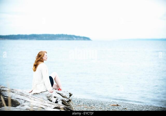 Young woman sitting on beach looking out to sea, Bainbridge Island, Washington State, USA - Stock Image