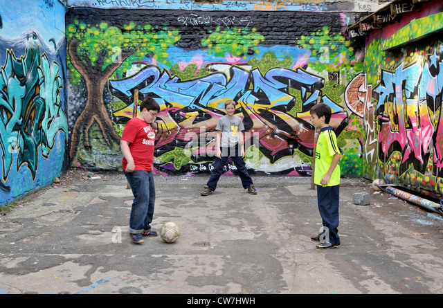 Serbian, German and Thai boys playing together soccer in the street, Germany, North Rhine-Westphalia, Cologne - Stock-Bilder