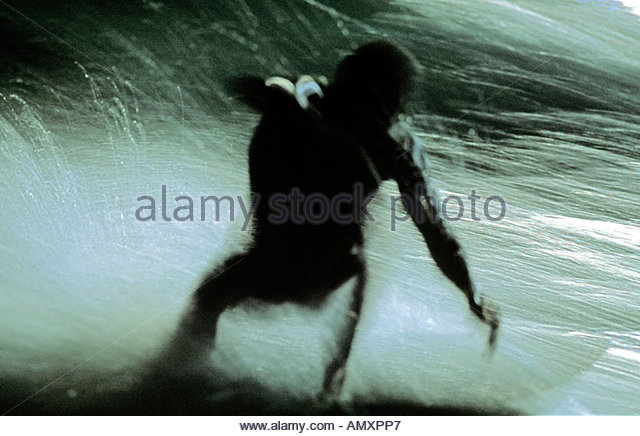 Surfer riding a wave at night Gold Coast Queensland - Stock Image
