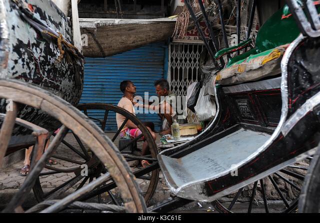 20.02.2011, Kolkata, West Bengal, India, Asia - A man gets shaved between rickshaws at a roadside in Kolkata. - Stock Image