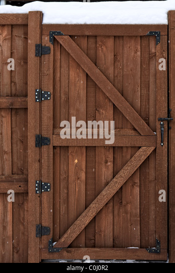 Wood fence gate in the snow - Stock Image