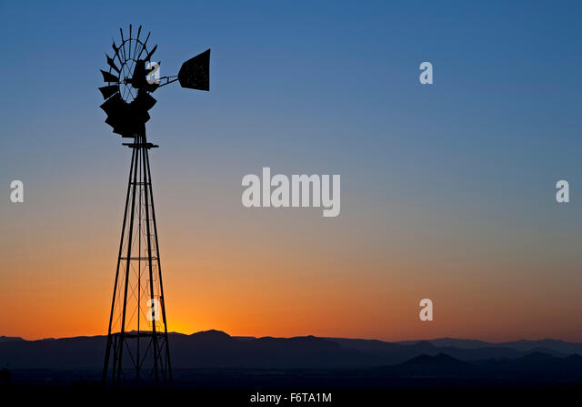 Windmill silhouetted against orange sky, Organ Mountains, near Las Cruces, New Mexico USA - Stock Image