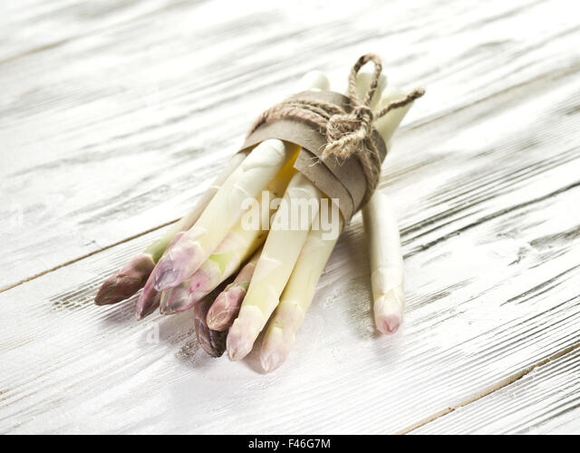 Shoots of white asparagus on the old wooden table. - Stock Image