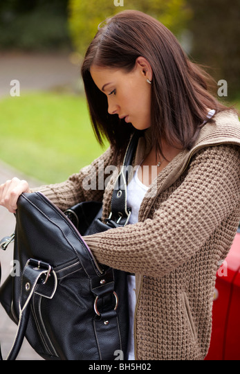 Woman looking in bag - Stock Image