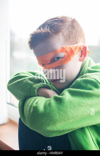 A 10 year old boy dressed as a superhero in an orange mask. - Stock Image