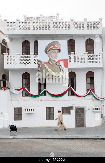 Man walking past a building adorned with a poster of the Sultan of Oman in Mutrah in Muscat, the capital of Oman. - Stock Image