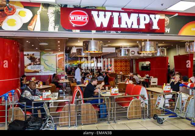 South Africa African Johannesburg O. R. Tambo International Airport terminal concourse gate area restaurant Wimpy - Stock Image