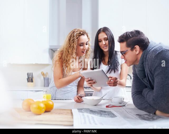 Three young adults using digital tablet at kitchen counter - Stock Image