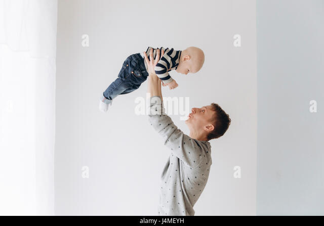 Caucasian father lifting baby son - Stock-Bilder