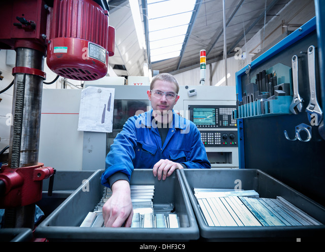 Apprentice engineer with components in factory, portrait - Stock Image