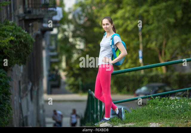 Young sporty girl after the workout standing outdoors. - Stock Image