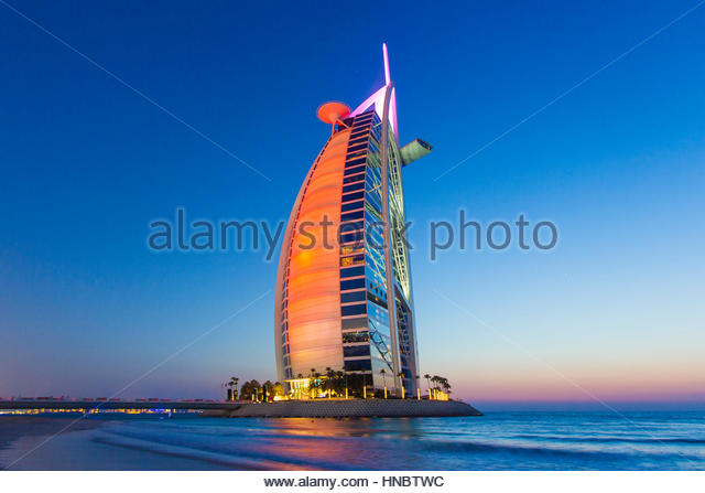 The Burj Al Arab hotel, on the Persian Gulf, ablaze in colorful reflections. - Stock-Bilder
