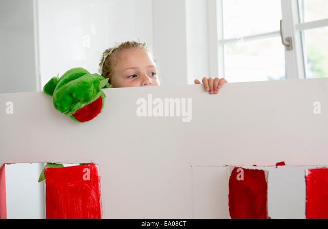 Girl peering over toy theatre with puppet - Stock Image