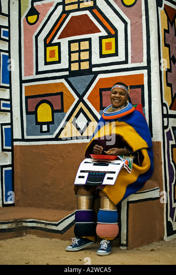Ndebele woman dressed in traditional costume Married woman Traditional geometric wall paintings in background South - Stock-Bilder