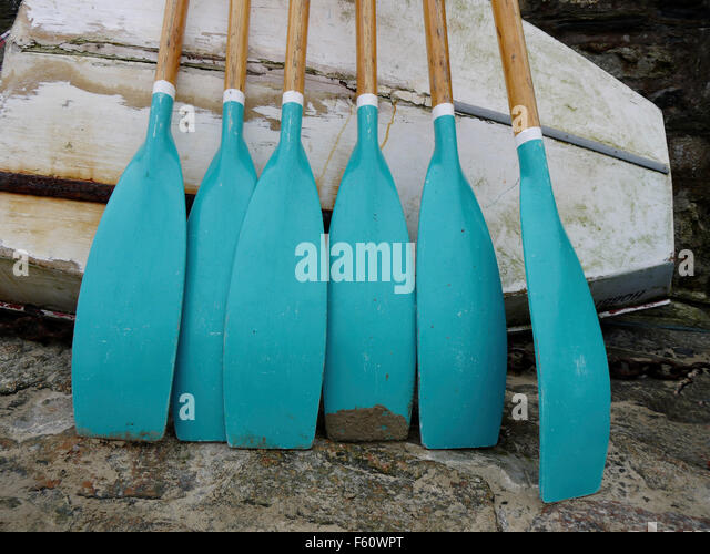 Cornish gig rowing oars resting against small boat - Stock Image