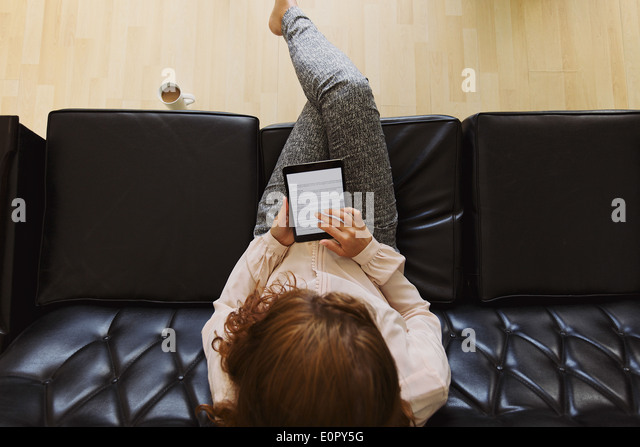 Top view of young brunette using digital tablet while sitting on a couch. Female reading a book - Stock-Bilder