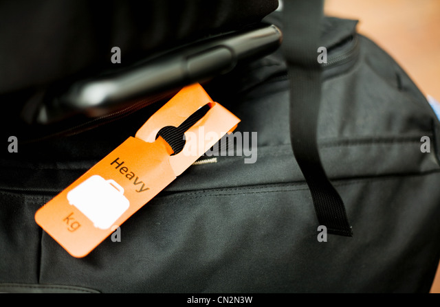 Holdall with label saying heavy - Stock Image