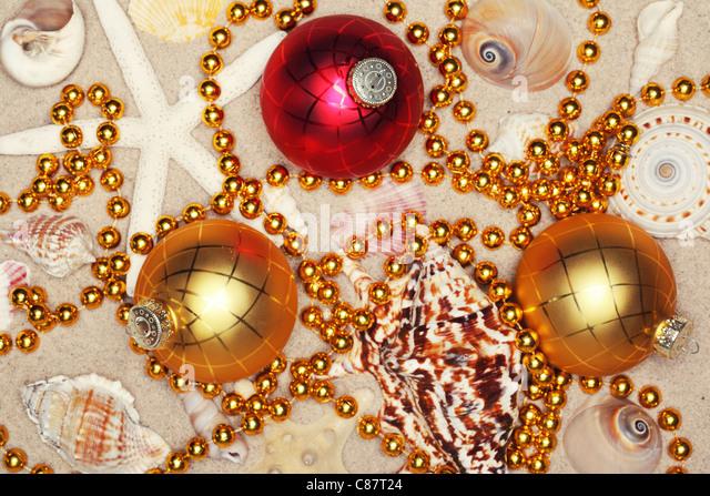 Christmas balls,seashells and beads on sands,Closeup. - Stock Image