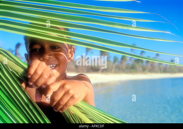 Young Fijian boy looking through palm frond Yasawa Islands Fiji South Pacific Ocean Model Released Image - Stock Image