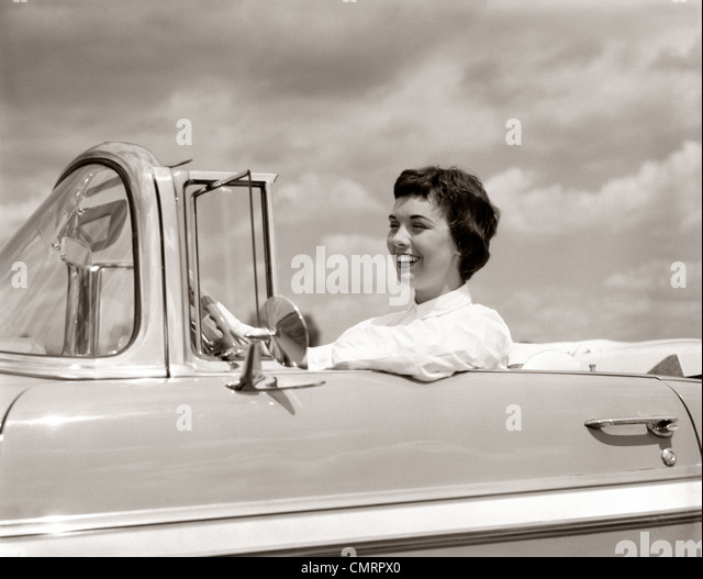 1950s SMILING WOMAN DRIVING CHEVROLET CONVERTIBLE AUTOMOBILE - Stock Image