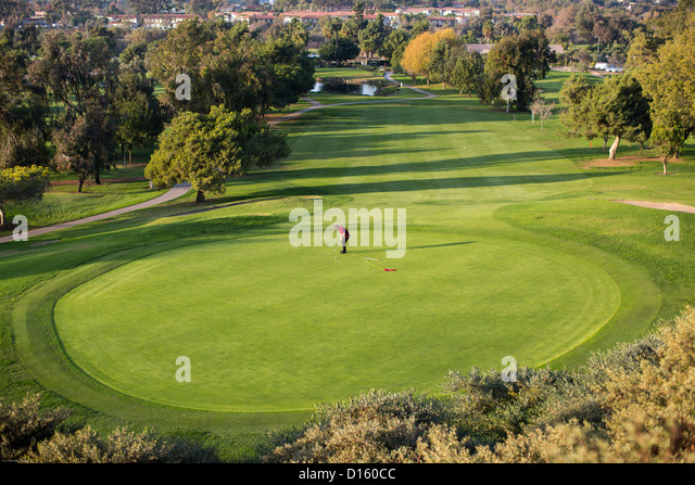 A golfer putts on a green at the San Juan Hills golf course in San Juan Capistrano, California. - Stock Image