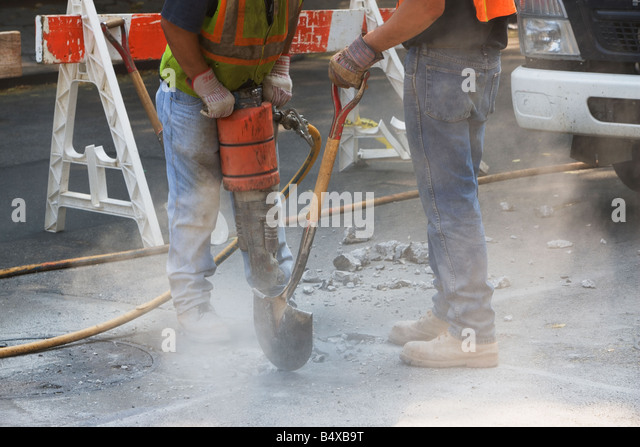 Construction workers using jackhammer and shovel - Stock Image