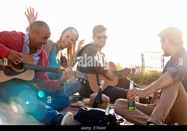 Four adult friends partying on Bournemouth beach, Dorset, UK - Stock Image