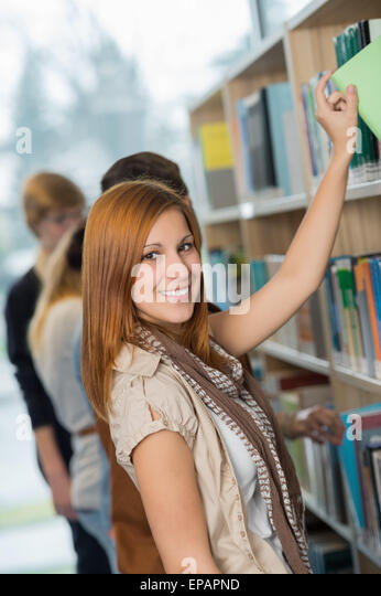 Student taking book from bookshelf in library - Stock Image