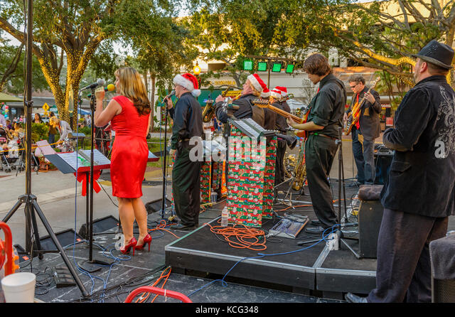 A band plays during the Christmas holiday in Hyde Park Village, an upscale neighborhood that includes shopping in - Stock Image