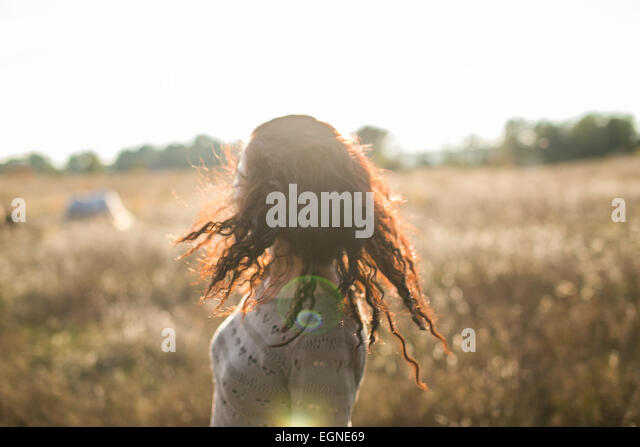 Young girl shaking her head on a walk in the field at sunset - Stock Image