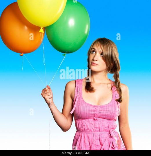 Teenage girl (16-17) holding bunch of balloons, portrait - Stock Image