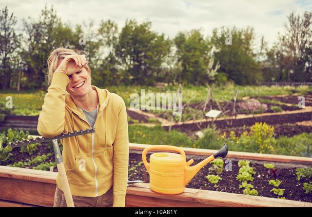 Mature woman, gardening, leaning on rake, laughing - Stock Image