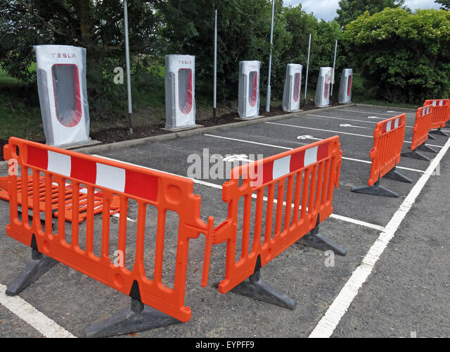 Tesla charging points being implemented on a motorway service area in the UK, with barriers around - Stock Image