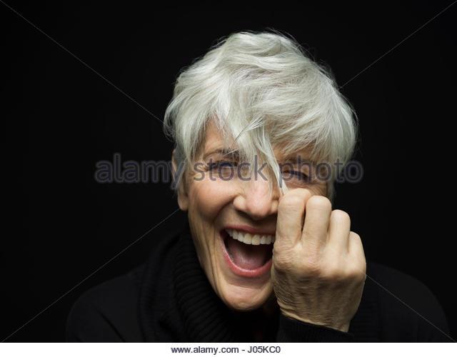 Close up portrait playful senior woman pulling short gray hair against black background - Stock Image